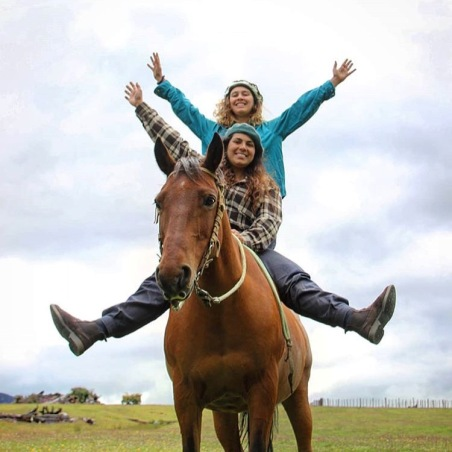 Two powerful women cheering and waving on a horse bareback